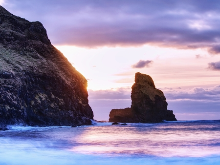 Sea stack sharp silhouette by sunset sky. Evening light on the rocks, boulders and cliff face of Talisker Bay, Isle of Skye Stock Photo