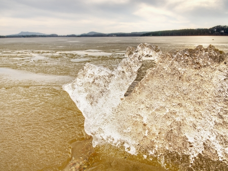 Winter natural wonder. Yellow pieces of snow melting on beach. Wonderful nature creation.