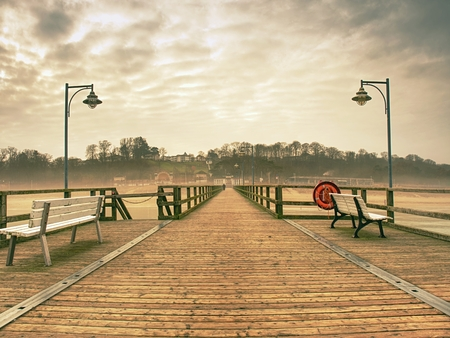 Old wood beach bridge in Goehren with nobody. Autumnal misty weather with cloudy sky.