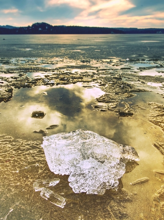 Heap of shining ice on beach.  Ice in a bay overlaid by night strong wind. Muddy beach with yellow brown icy floes Archivio Fotografico