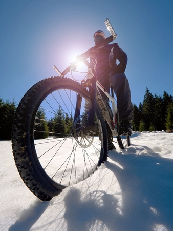 Wide view photo of mountain bike in deep snow. Winter mountains with road lost under snow.