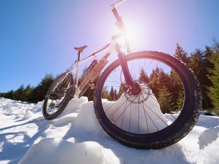 Close wide view to mountain bike stays in snow. Winter snowy mountains with road between trees. Stock Photo