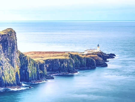 Neist Point peninsula with lighthouse, tourist destination on Isle of Skye, Scotland. Foamy blue sea strikes against the sharp cliff.  All travelers must see