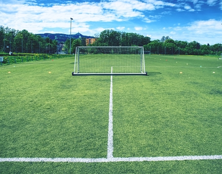 On football soccer field. Behind goal of soccer field. Soccer football net background over green grass or soccer field and blurry stadium and soccer players.