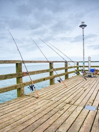 Fishers rods against handrail of wooden bridge.  Fishing on harbor mole. Overcast day, with the hidden sun. Stock Photo