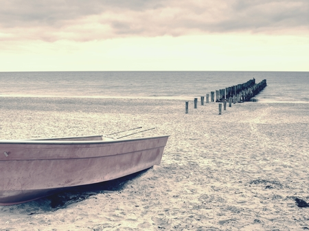 Abandoned fishing paddle boat on sandy beach. Quiet sea water level during morning windless.
