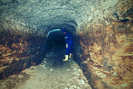 Underground work. Hunched worker in a blue overall and a safety helmet stands in the underground tunnel. The staff check the underground unsupported  mine.