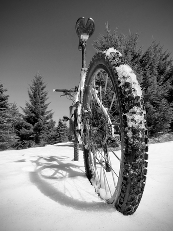 Cycling in winter snowy mountains on large tire wheels mountain bike. Sunny winter day.