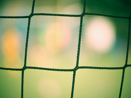 Detail on a soccer net and ball waiting on turf. Soccer goal. Sports background