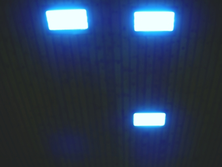 Luminous ceiling of square tiles. Wooden ceiling with lighting panels. Fluorescent lamps on the modern ceiling.