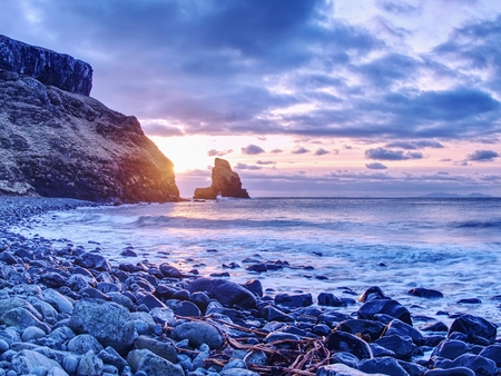 The rest of the day in rocky bay. Evening light on the rocks, boulders and cliff face of Talisker Bay, Isle of Skye Stock Photo