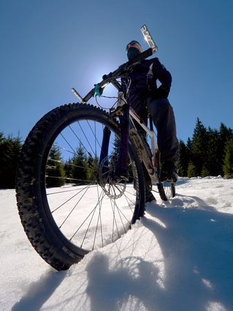 Mountain bike standing in frozen snow against blue sky. Hidden  asphalt road under sow cover. Extreme adrenalin sports Stock Photo