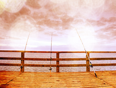Abstract effect.  Several fishing rods against the wooden railing of the beach pier. Overcast day, with the hidden sun.