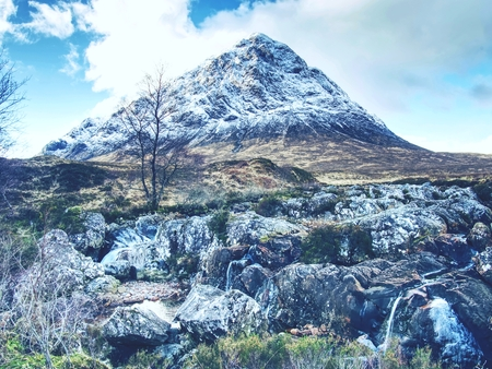 Winter trek. Buachaille Etive Mor in Glencoe, t he highlands of Scotland. Sunny winter day.