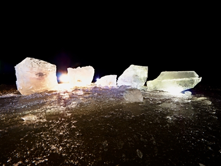 Blocks of shining ice and snow on the shore. The floes and crushed ice  during the evening and dark  hours when the ice at sea breaks up.