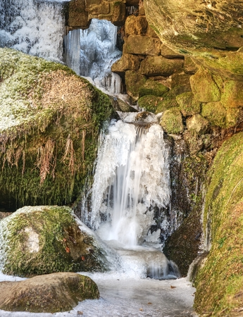 Icicles in frozen waterfall. Snowy and icy stones and boulders with drops of fallen chilly water between sandstone rock. Stock Photo