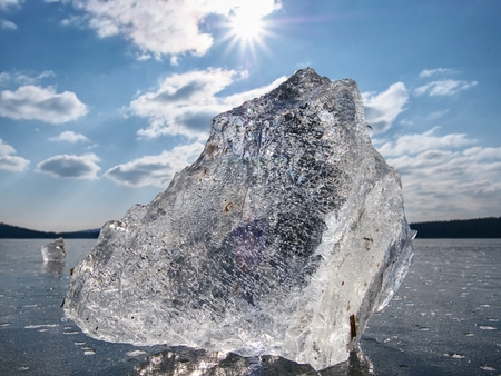 Beautiful transparent piece ice of Lake against dark blue sky and  bright sun. Stock Photo