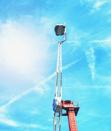 Big swing in over Sky. Fairground ride  against a blue summer sky