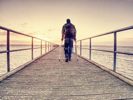 Hurt man with hooded jacket and forearm crutches  standing on sea bridge within  early morning and thinking. Gloomy nostalgic silhouette of sad lonely melancholic adult.