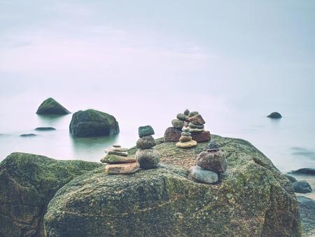 Stones pyramid symbolizing zen harmony balance pebbles. Peaceful ocean in background. Colorful flat stones for meditation.
