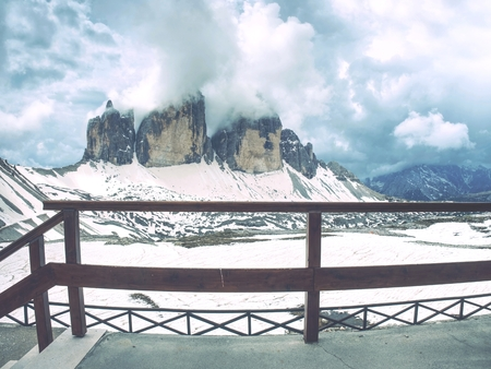 Breathtaking view from mountain hut terrace to symbol of Italian Dolomites - Tre Cime. High rocky ridge touching  clouds above snowy base. Tre Cime di Lavaredo National Park, Italy