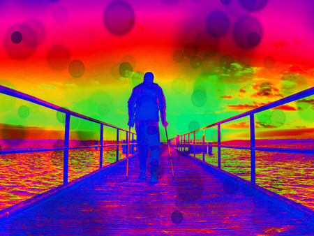 Hurt man on pier in the sunrise. The wharf construction above sea follow  Sun. Hipster filter.