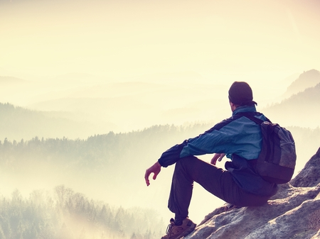 Hiker is enjoying sunrise view in hilly landscape. Male hiker sitting and relaxing at the rocky summit of sharp mountain Stock fotó