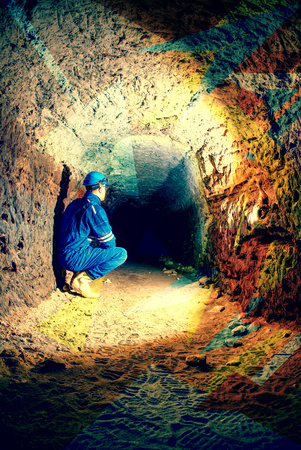 Man worker checking something in abandoned mine tunnel. Underground job. Hipster filter.