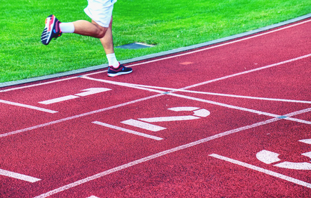 Male athletes are running on outdoor stadium track. Red rubber running tracks with numbers and wwhite lines of the stadium. Stock Photo