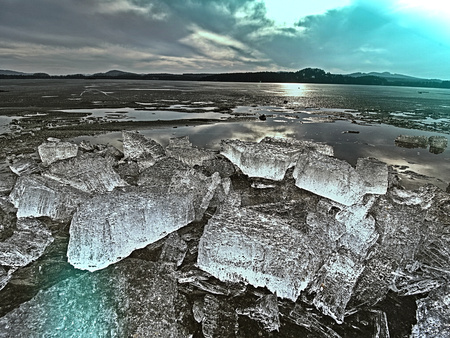 Transparent ice piece on the lake with color effects. Crystal clear piece of ice squeezed the lake. Hipster filter. 免版税图像
