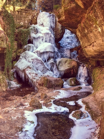 Winter frozen waterfall. Small pond and snowy boulders bellow cascade of waterfall. Crystal freeze water of mountain river and sounds of falling water.