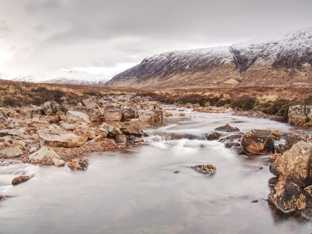 Mystic atmosphere awithin trek t River Etive in Glencoe moutains In Winter.  Cold windless winter morning