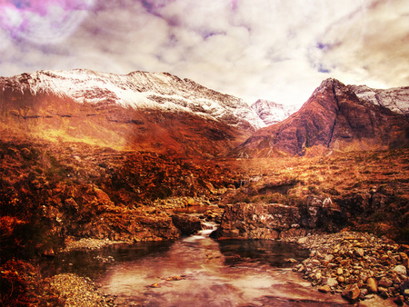 Popular trek. Waterfall between sharp exposed rocks, the Fairy pools on the Isle of Skye, Scotland.   Hipster filter. 스톡 콘텐츠