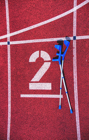 Forearm crutches on red running track number on stadium. Lines on front tracks