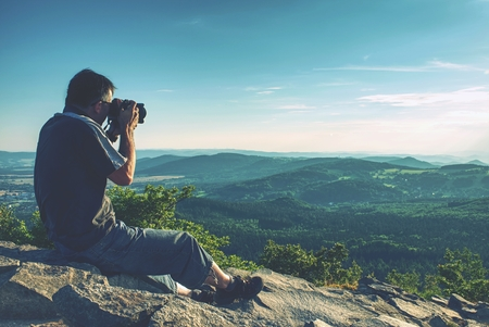 Photographer taking authentic outdoor photos in autumn landscape by big dslr camera. Travel photo lifestyle.