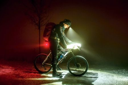 Extreme Sport race.Winter Enduro Biking challenge. Biker check possition in map. Lost way under fresh snow. Winter misty night with snow.