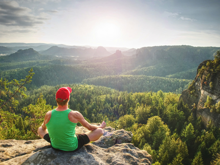 Man meditates in yoga position in mountains above wild nature at sunset. Concept of meditation, spirituality and  soul balance