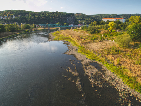 Dry riverbed of river Elbe in Decin, Czech Republic, summer 2018. Empty river bed with poisoned muddy water. Decin castle above old railway bridge. Stock Photo