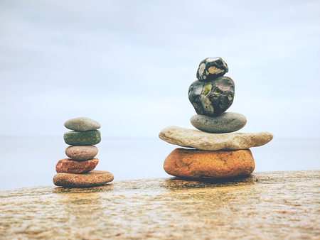 Stack of stones on beach - nature background. Stone cairn on blue blurry background. Colorful  pebbles and stones