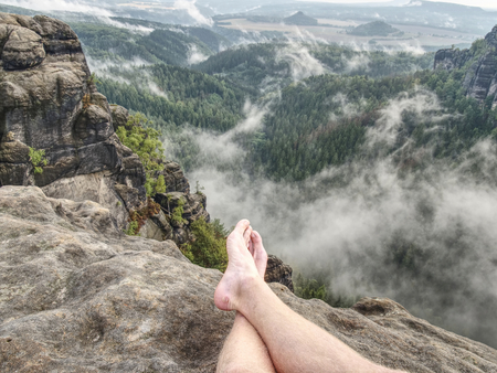 The crossed legs take a rest on tiring mountain trail. Sweaty male legs without trousers relaxing on peak of mountain above valley.