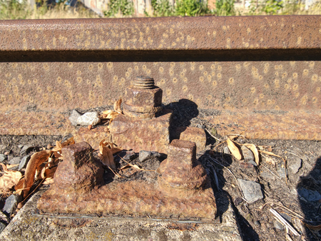 Detail of rusty screws and nut on old railroad track. Rotten tie with rusty nuts and bolts. Terrible smell extracted old wooden ties with phenol asphalt paint.