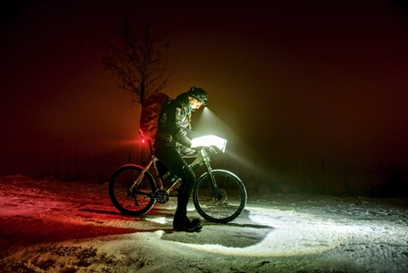 Extreme winter mtb race. Cyclist man with winter bike stays in snow and check the paper map under headlamp. Winter extreme sport, sportive concept.