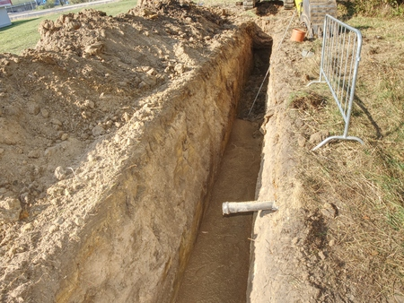 Repairing of plastic tube water delivery system. Open trench with small diameter water pipe and heap of ground near. Excavation of trench by hand or mechanized excavator and installation. Stock Photo