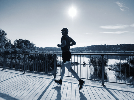 Side shot of healthy middle age man running on lake promenade in sunny morning. Male runner sprinting outdoors. Down angle view Imagens