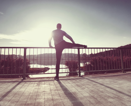 Tall sportsman warming up his muscles, stretching his legs before running workout in the morning. Sunny morning outside at mountain lake