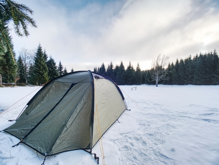 Trekking tent built  against the snowy landscape. Winter skialpinism trek over snowy mountain peaks.