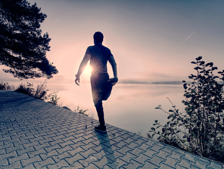 Runner sprints along the lake. Freeze sportsman in running pose.Morning moody atmosphere.