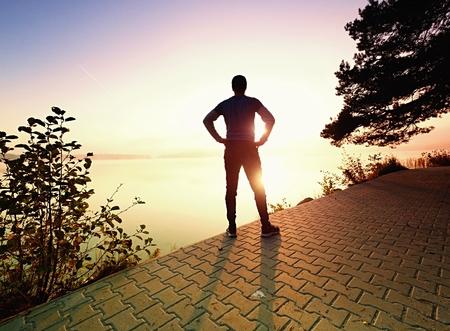 Active sport man runner stretching body on pavement lake side, regular outdoor training for marathon