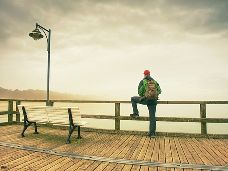 Pensive guy in trekking suit on a wooden pier over the water. Tourist at dusk on the docks bridge and looking afar.