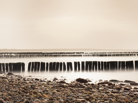 Incoming waves hitting vintage old wood at the coast. Long exposure at sunset of pier pilings